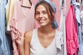 Glad Female Model Standing Between Clothes Hanging On Rack, Smiling Broadly Being Glad To Have Varie poster