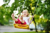 Cute Little Girl Having Fun On A Playground Outdoors On Warm Summer Day poster