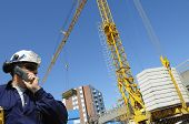 foto of construction crane  - construction engineer in front of mobile crane inside building - JPG