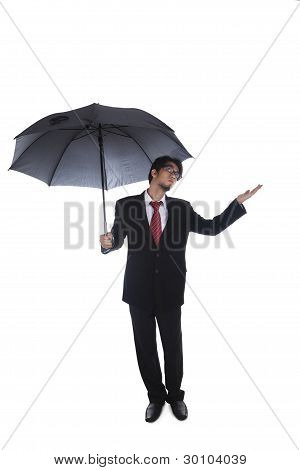 Businessman Holding Umbrella With Hand Held Out