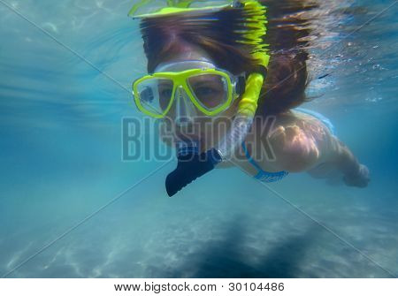 Young woman snorkeling in a clear sea