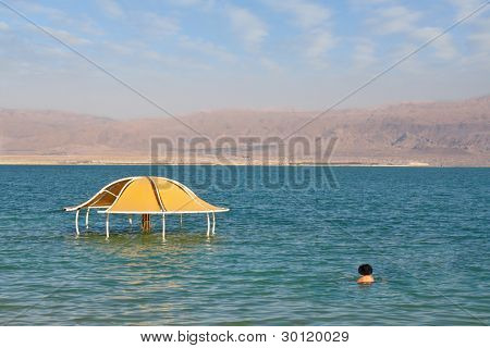 The brave bather plunged into the cool water from the Dead Sea. Sunny beach on the Dead Sea. A wonderful warm day in December. The beach pavilion is half flooded with seawater risen