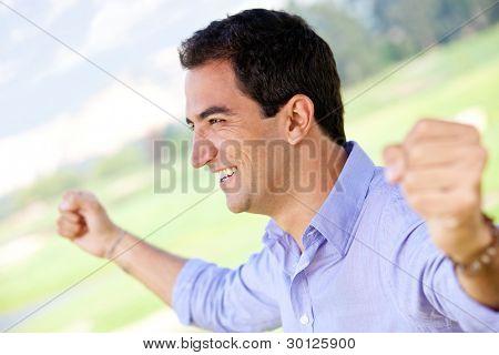 Hombre excitado celebrando su victoria con los brazos hacia arriba