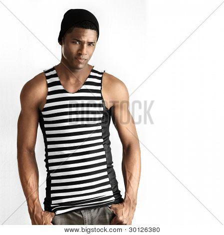 Fashion portrait of fit young male model in black and white striped trendy sleeveless shirt against white neutral background with copy space