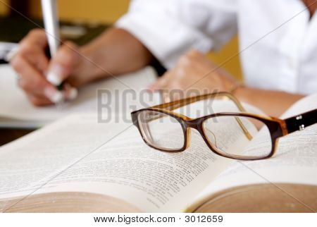 Researcher Writing With Glasses