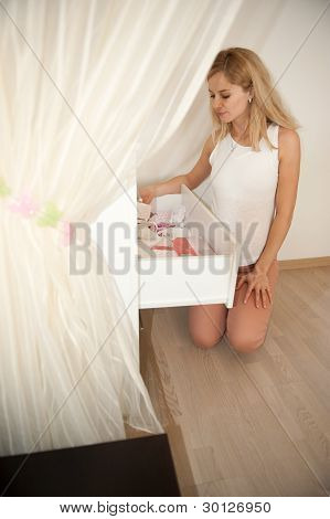 Pregnant Blonde Near Chest Of Drawers