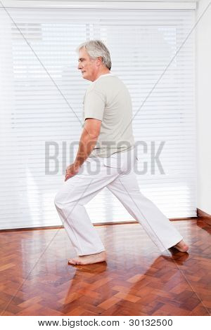 Active senior man stretching in gym before fitness training