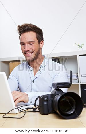 Professional photographer with camera and laptop computer in office