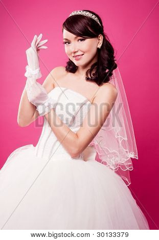 beautiful happy bride putting on gloves, isolated against pink studio background