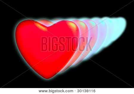 A Series Of Decreasing Hearts With Neon Light On A Black Background.