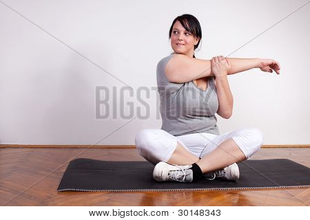 Overweight Woman Stretching At Home