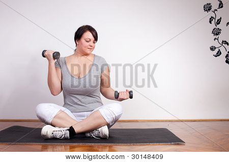 Plus Size Woman Lifting Weights At Home