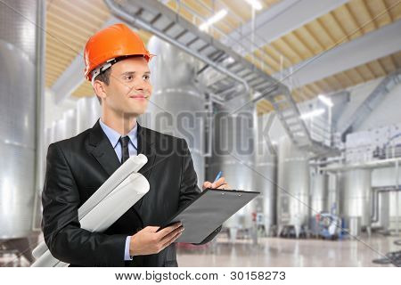 A construction worker with helmet holding blueprints and writing on a clipboard in a factory