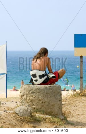 Joven Surfer Dude esperando las olas y el viento de la cometa