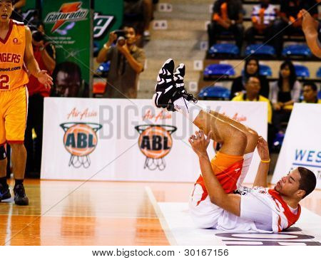 KUALA LUMPUR - FEBRUARY 19: Malaysian Dragons' Brian Williams falls from a foul at the ASEAN Basketball League match against Singapore Slingers on Feb 19, 2012 in Kuala Lumpur, Malaysia. Dragons won 86-71.