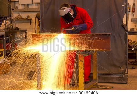 Welder Bends To Cut Metal Beam.