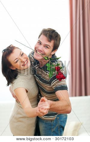 Happy Young Couple Dancing With Red Rose At Home