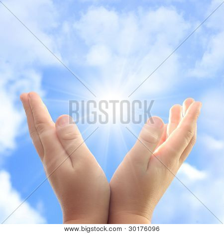 Child hands against blue sky and sun.