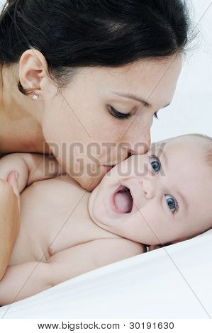 Mother And Daughter Playing Happily On White Bed