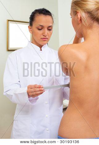 Female doctor in white uniform examine woman breast