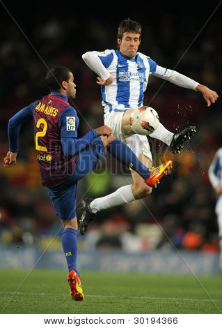 BARCELONA - FEB 4: Mikel Aramburu (R) of Real Sociedad vies with Dani Alves(L) of FC Barcelona during the Spanish league match at the Camp Nou stadium on February 4, 2012 in Barcelona, Spain