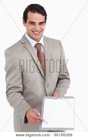 Smiling salesman asking for signature against a white background
