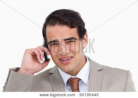 Close up of annoyed young salesman on his cellphone against a white background