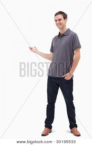 Happy man standing and presenting something behind against white background
