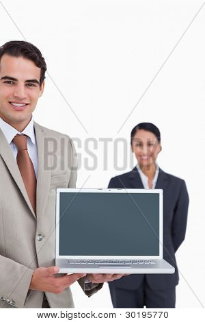 Laptop being presented by smiling salesman with colleague behind him against a white background