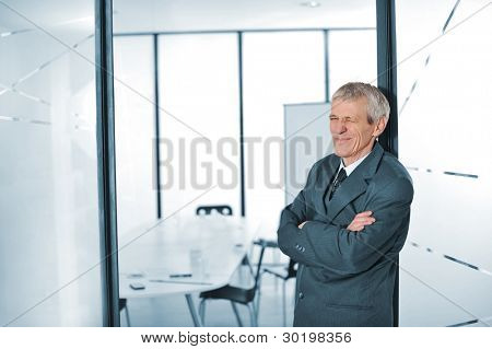 Elderly business man winking with folded arms