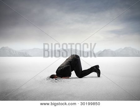 Businessman hiding his head in the sand