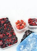 pic of tupperware  - Plastic containers of frozen mixed berries in snow  - JPG