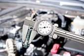 stock photo of micrometer  - A shiny vernier caliper micrometer in front of a car engine during for servicing and repair - JPG