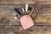 Things From Open Lady Purse. Cosmetics And Womens Accessories Fell Out Of Handbag On Old Wooden Bac poster