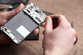 Technician Fixing Mobile Phone At Table, Closeup. Device Repair Service poster