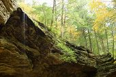pic of fall trees  - Small waterfall running off large rock cliff - JPG