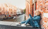 Young Woman Tourist Sits On A Bridge In The Old City In Bruges In The Morning In Belgium And Waves A poster