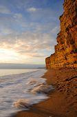 Постер, плакат: Танцы волны и Золотой песчаниковые скалы на пляже куст Бертон Bradstock вблизи Бридпорт Дорсет