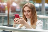 Indoor Shot Of Attentive Serious Fair Haired Girl Holding Smart Phone In Ger Hands, Looking At Its S poster