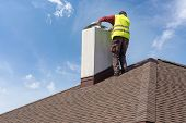 Skilled Workman In Protective Work Wear And Special Uniform Install Chimney On Roof Top Of New House poster