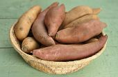foto of batata  - Basket of red yams and sweet potatoes on green table