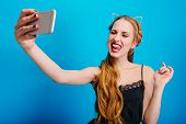 Gorgeous Young Woman Taking Selfie, Making Funny Facial Expression, Showing Tongue To Camera, At Par poster