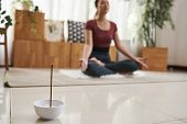 Small Ball With Burning Aroma Stick On Floor Of Young Meditating Woman poster