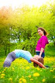 Girl Practicing Stretching Exercises. Beautiful Young Women Doing Stretching Exercise On Green Grass poster