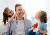 Happy fathers day! Children daughters congratulating dad and giving him postcard. Daddy and girls s poster