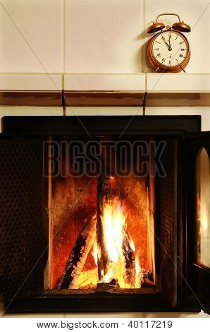 Fireplace And  Old-fashioned Copper Alarm Clock On The Mantelshelf