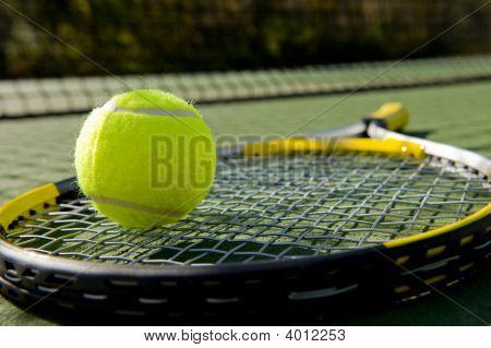 Tennisschläger und Ball auf Platz