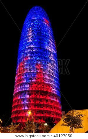 BARCELONA, SPAIN - AUGUST 15: Torre Agbar illuminated with the Barca team colors at night on August 15, 2012 in Barcelona, Spain. This 38-storey tower was designed by the famous architect Jean Nouvel