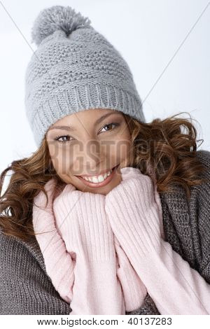 Beautiful ethnic girl smiling happily in winter outfit, wearing hat.
