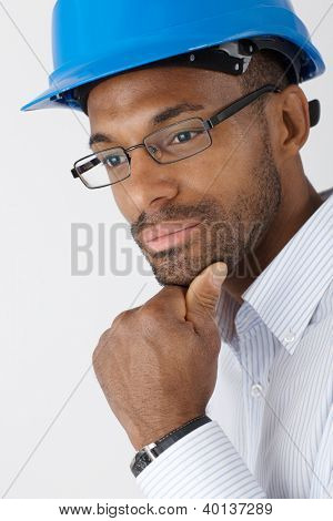 Closeup portrait of ethnic engineer in hardhat thinking.